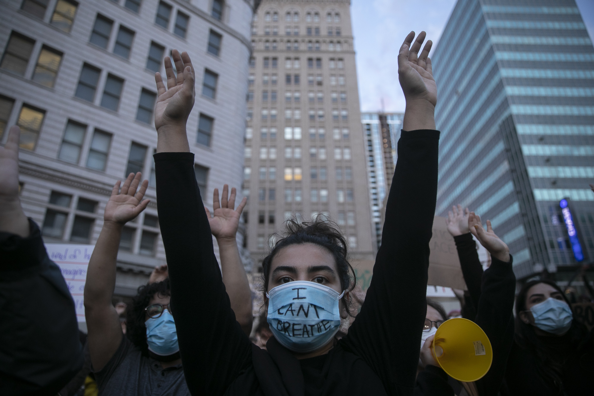 A protester wears a surgical mask with 'I can't breathe' written on the front as an organizer asks demonstrators to put their hands up on May 29, 2020 Downtown Oakland. Thousands took to the streets Friday night in solidarity with protesters in Minneapolis against the killing of George Floyd by Minneapolis police earlier this week. Photo by Anne Wernikoff for CalMatters