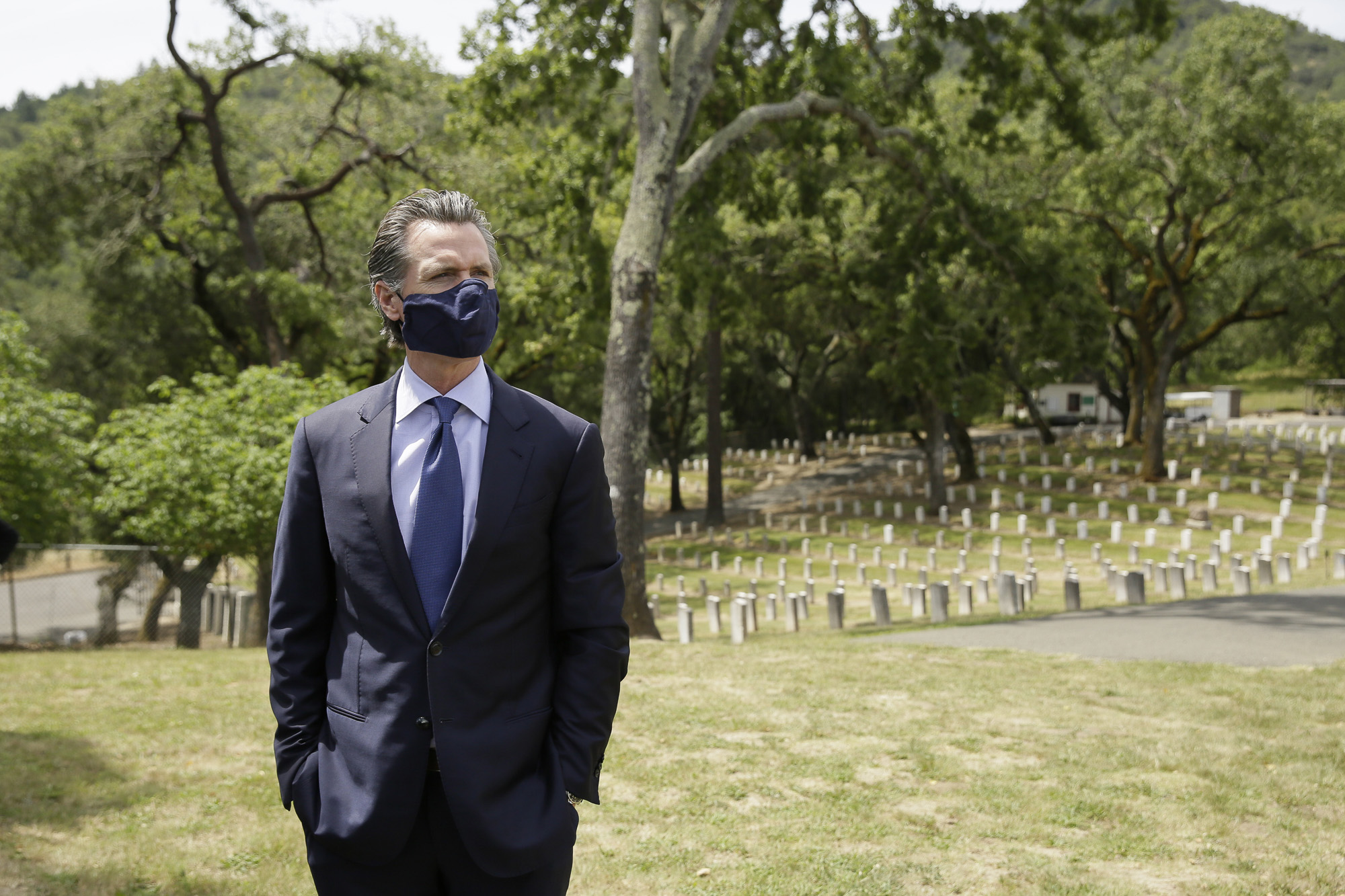 California Gov. Gavin Newsom looks out at rows of graves before a wreath laying ceremony in the cemetery at the Veterans Home of California May 22, 2020, in Yountville. Photo by Eric Risberg, AP Photo/Pool
