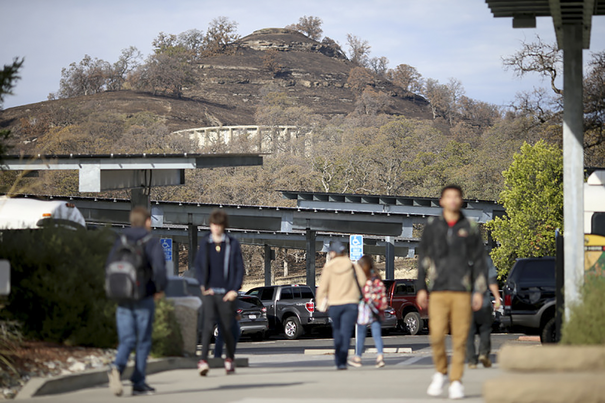 Butte College students walk onto campus as classes resume while a hillside behind the school shows just how close the wildfire got in Oroville, Calif., on Nov. 26, 2018. The community college had 431 students and 116 faculty and staff impacted by the Camp Fire. Photo by Anda Chu/Bay Area News Group