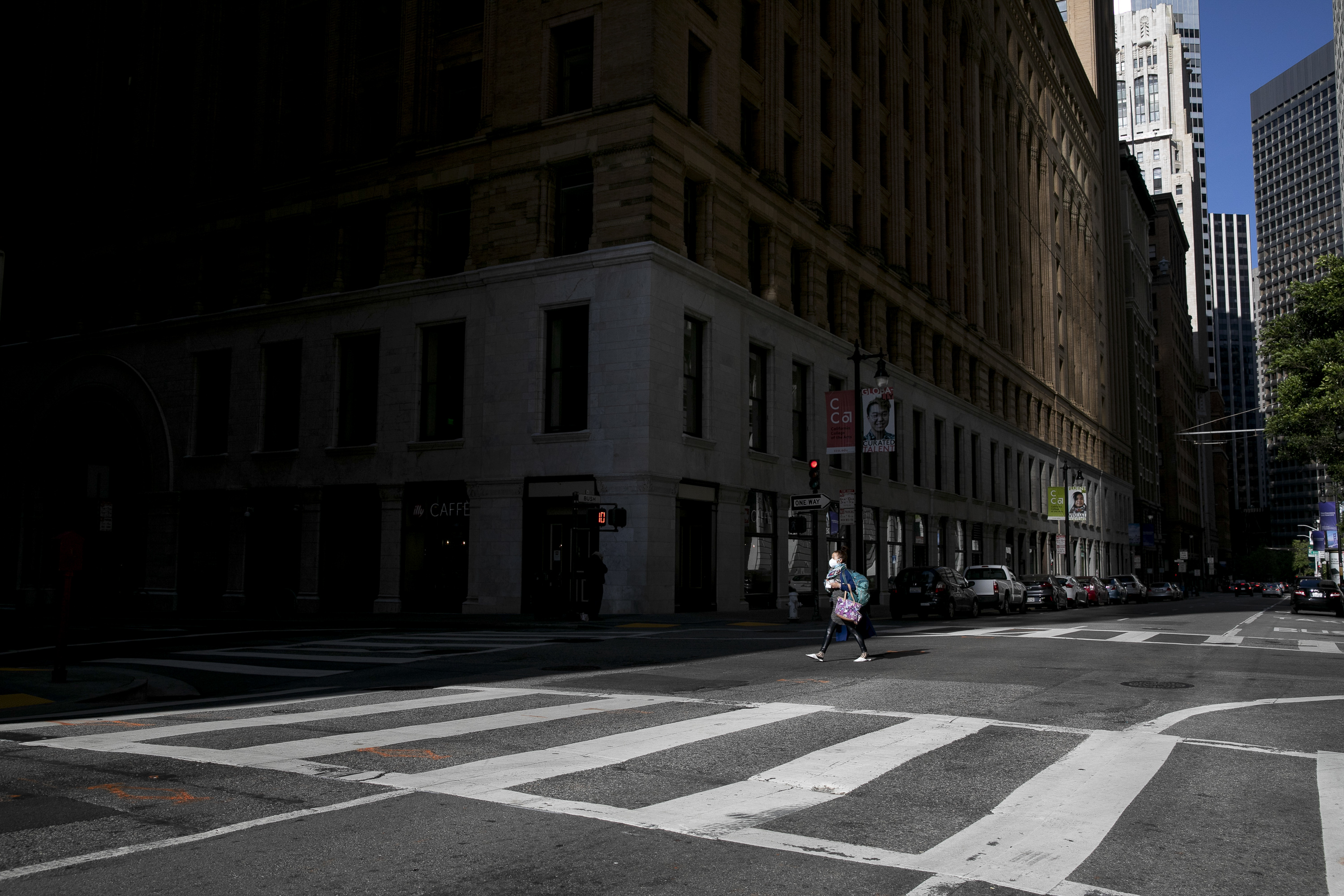 A pedestrian crosses an empty intersection in San Francisco financial district at evening rush hour on May 7, 2020. San Francisco county has announced they will maintain shelter in place orders through the end of May. Photo by Anne Wernikoff for CalMatters