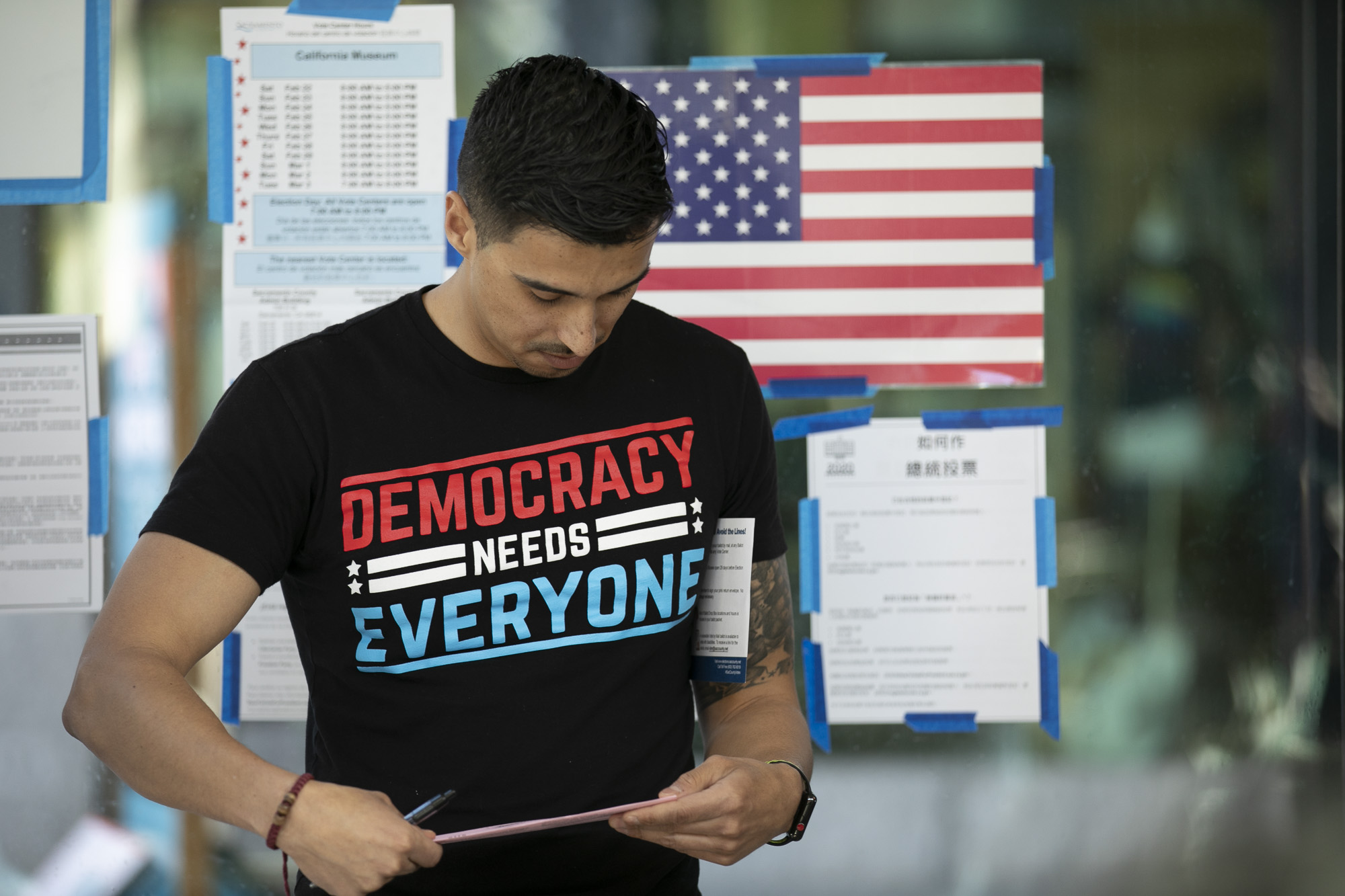 Esteban Nunez seals his vote-by-mail envelope before submitting his ballot for the presidential primary at the California Museum in Sacramento on March 2, 2020. Photo by Anne Wernikoff for CalMatters