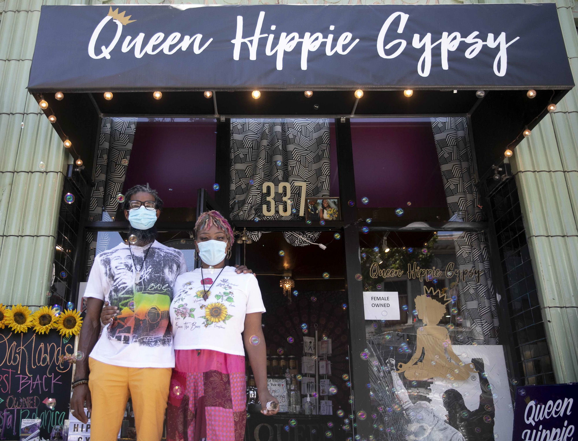 Kyrah Ayers, left, and his wife, Lilliannia Ayers, stand in front of her shop Queen Hippie Gypsy in downtown Oakland. The shop, which opened two years ago, was one of several on their block to be vandalized earlier this week during protests against the killing of George Floyd by police in Minneapolis. Photo by Anne Wernikoff for CalMatters
