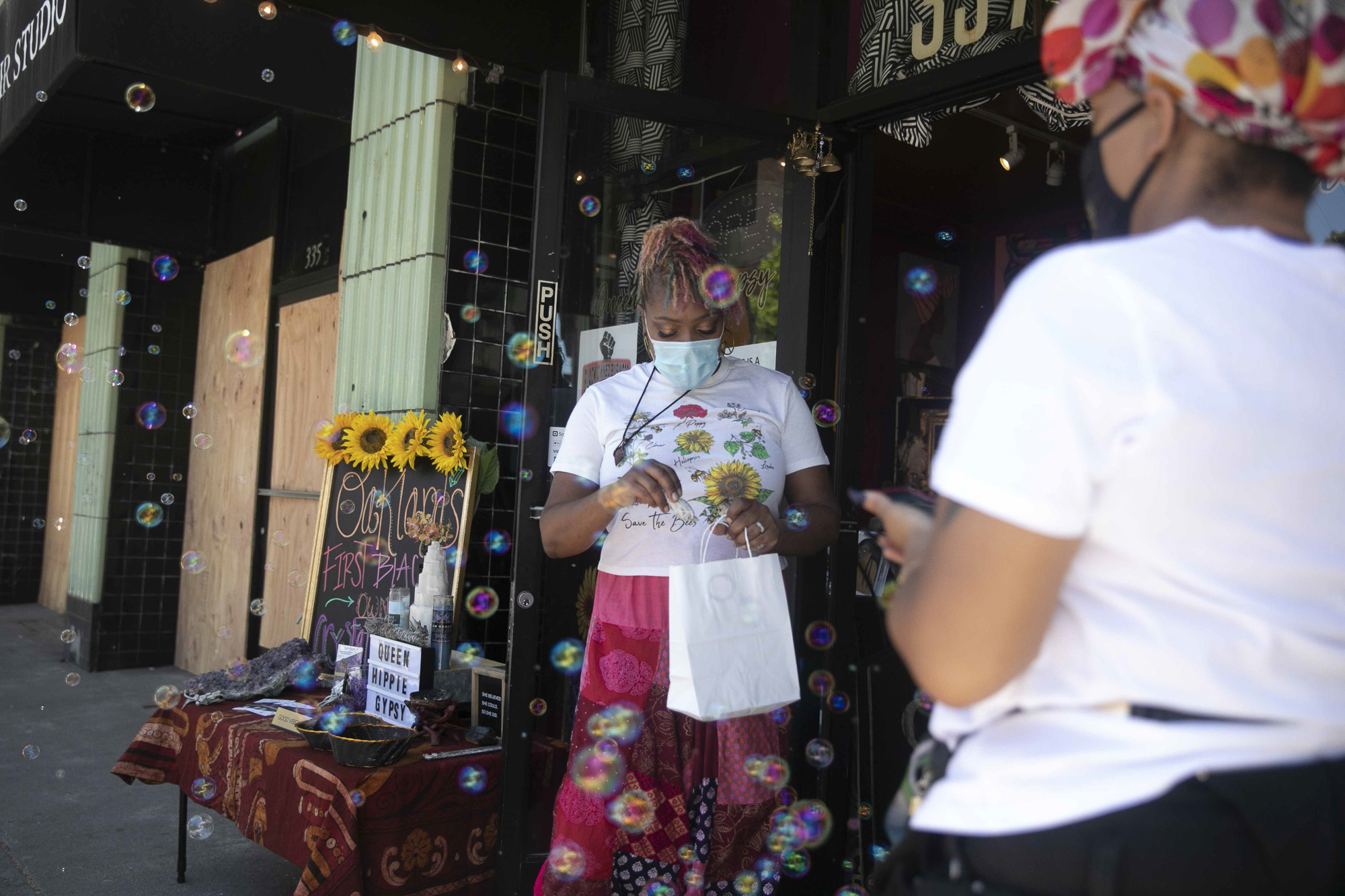 Lilly Ayers places a stick of sage in a bag while serving a customer at her store Queen Hippie Gypsy in downtown Oakland. All of the small businesses on Ayers' block were damaged during California protests over the killing of George Floyd Minneapolis police.. Photo by Anne Wernikoff for CalMatters