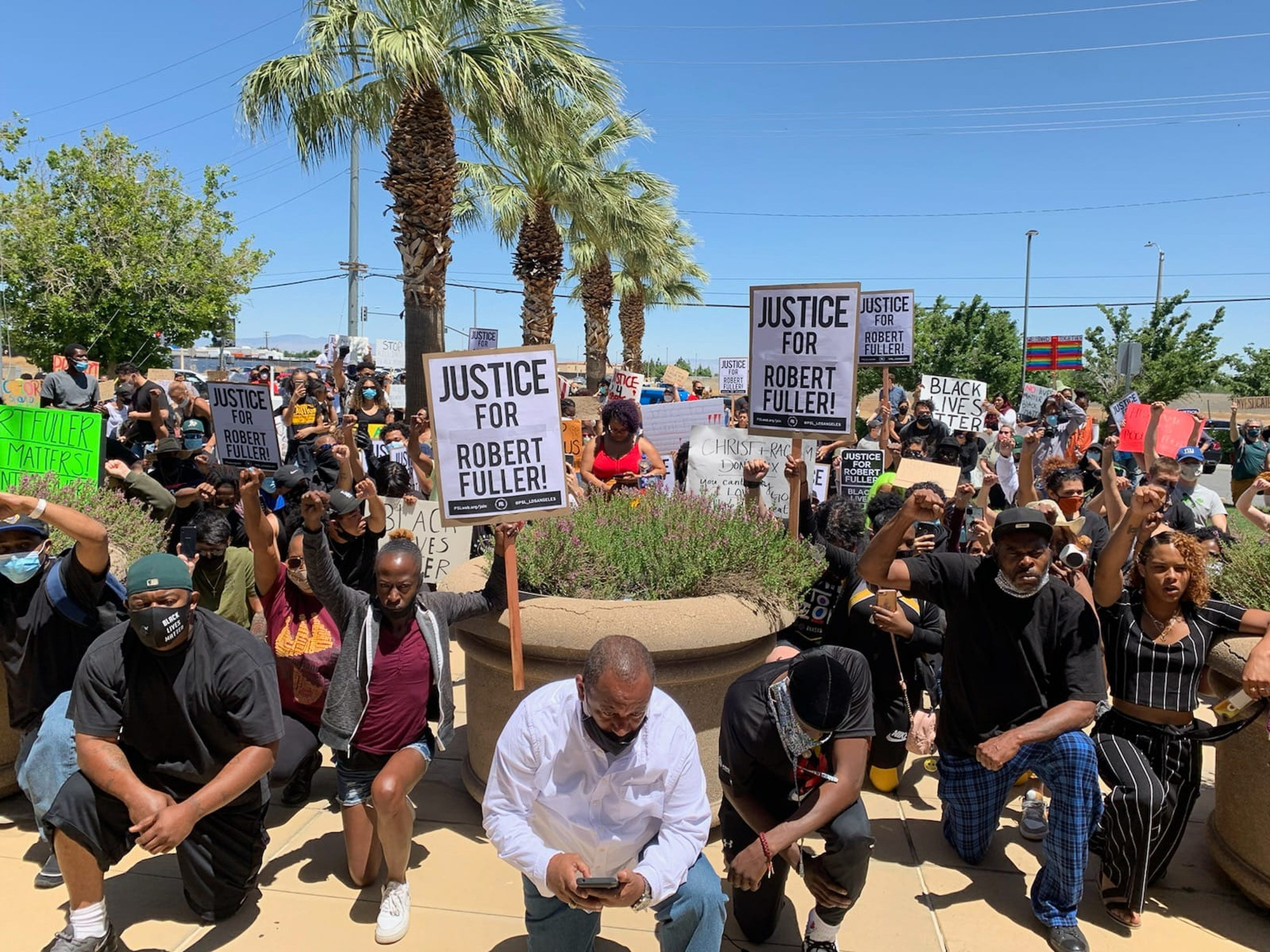 Activist Najee Ali, center, kneels with weekend demonstrators in front of the Palmdale Sheriff's station as protesters demand an investigation into the death of 24-year-old Robert Fuller, who was found hanging from a tree early Wednesday. On Monday, state Attorney General Xavier Becerra agreed to get the state involved. Photo by Josie Huang/KPCC/LAist via AP
