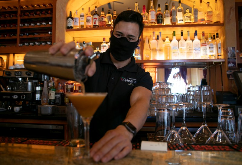 A masked bartender pours a drink at Ristorante Allegria in downtown Napa on May 22, 2020 as restaurants were permitted to reopen for indoor dining. Today, Gov. Newsom announced the closure of all indoor dining, bars and movie theaters state-wide. Photo by Anne Wernikoff for CalMatters