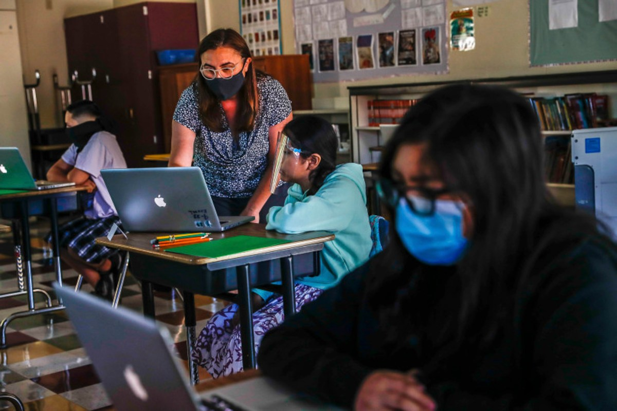Teacher Jessica DeAnda, left, instructs Liz Valdez, 11, center, as Kayla Torres, 11, right, works on her laptop at Sunrise Middle School on June 22, 2020 in San Jose, the first Bay Area school to reopen since shelter-in-place was announced in March. Photo by Randy Vazquez, Bay Area News Group